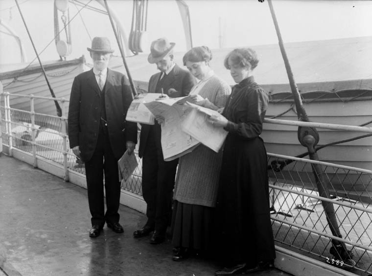 Black and white photograph of four people standing on the deck of a ship