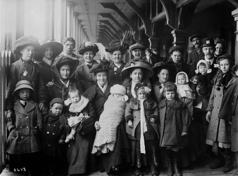 Black and white photograph of a group of men, women and children stading outside a building