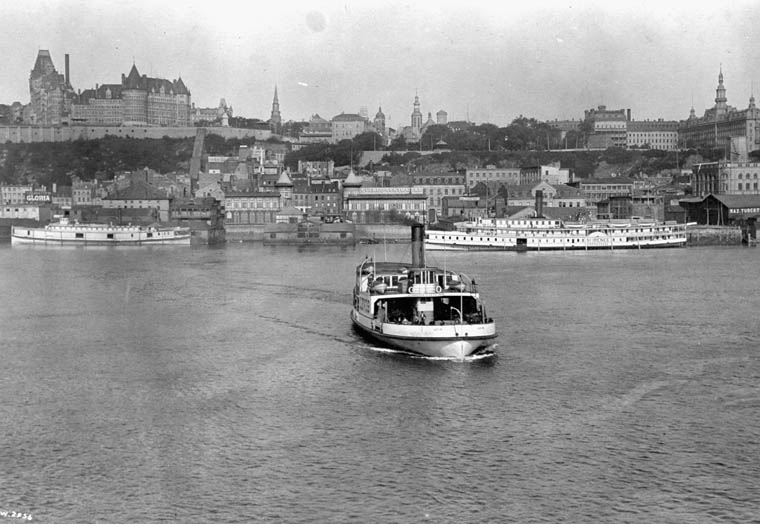 Black and white photograph of three steamships at the harbour beneath the old town of Quebec City