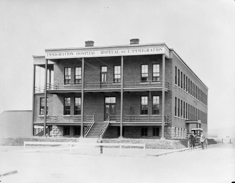 Black and white photograph of a three-storey brick building with a large sign reading