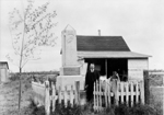 Black and white photograph of a man standing beside a stone monument in front of small house