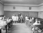 Black and white photograph of a classroom interior with a male teacher and seven students standing at the front. There are blackboards on two sides of the room and students sitting in desks.