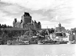 Black and white photograph of steamboats docked at a river harbourfront with a palatial building on a cliff in the background