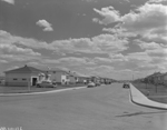 Black and white photograph of a street, showing houses on either side