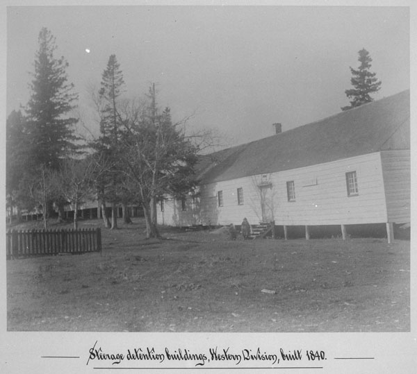 Black and white photograph of long wooden buildings surrounded by trees