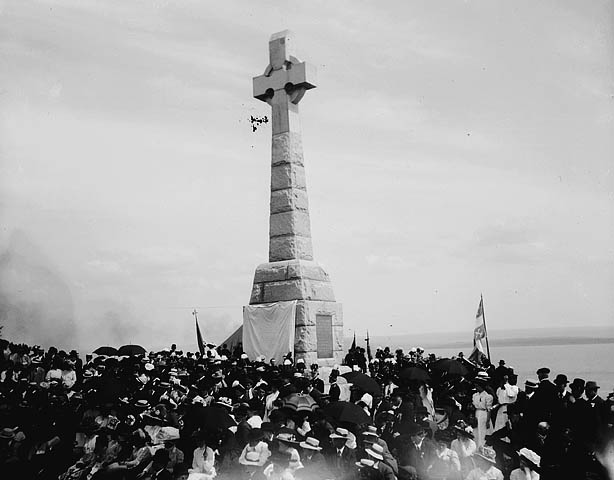 Black and white photograph of a crowd beneath a stone monument with a large celtic cross