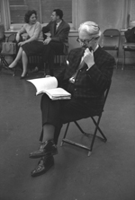 Black and white photograph of a man sitting on a chair reading a book