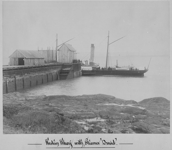 Black and white photograph of a small steam ship docked at a small wharf