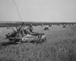 Black and white photograph of a threshing machine on a prairie field and bales of hay in the distance